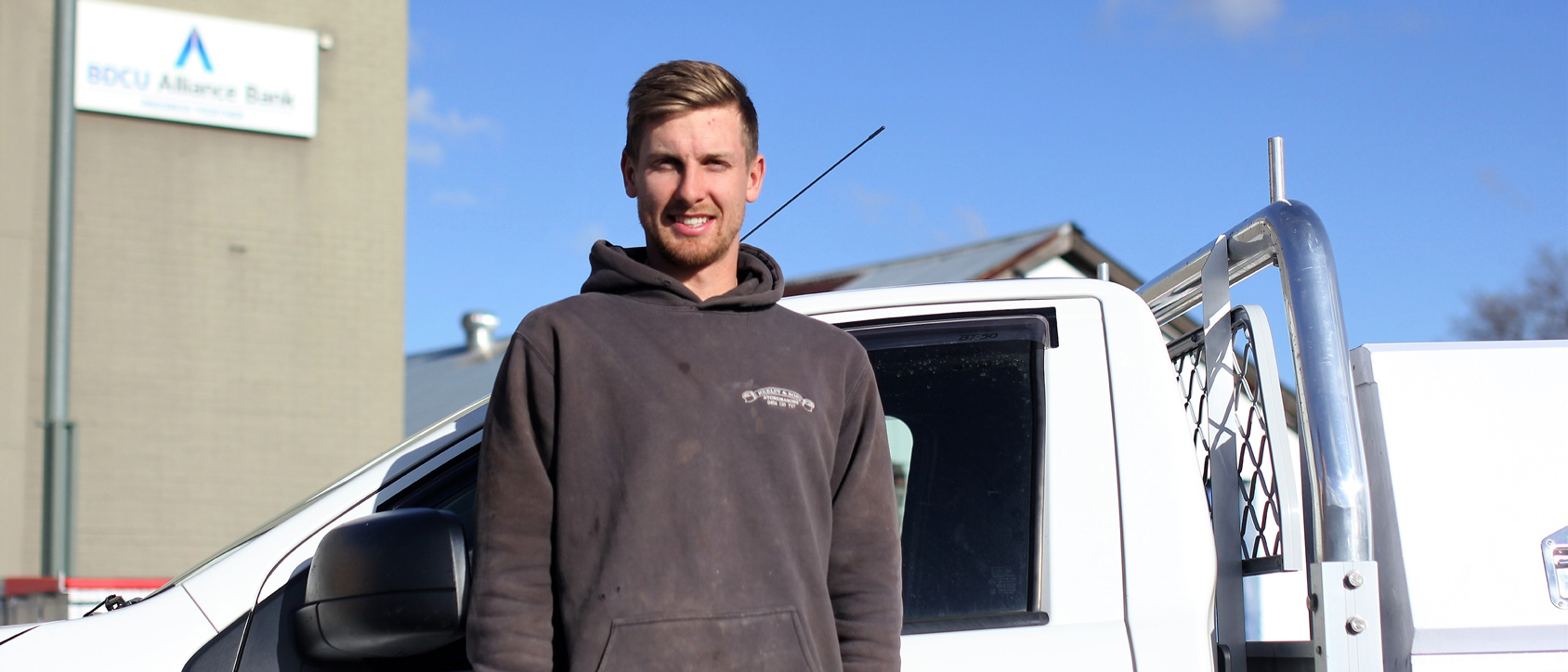 An apprentice standing in front of his new ute.