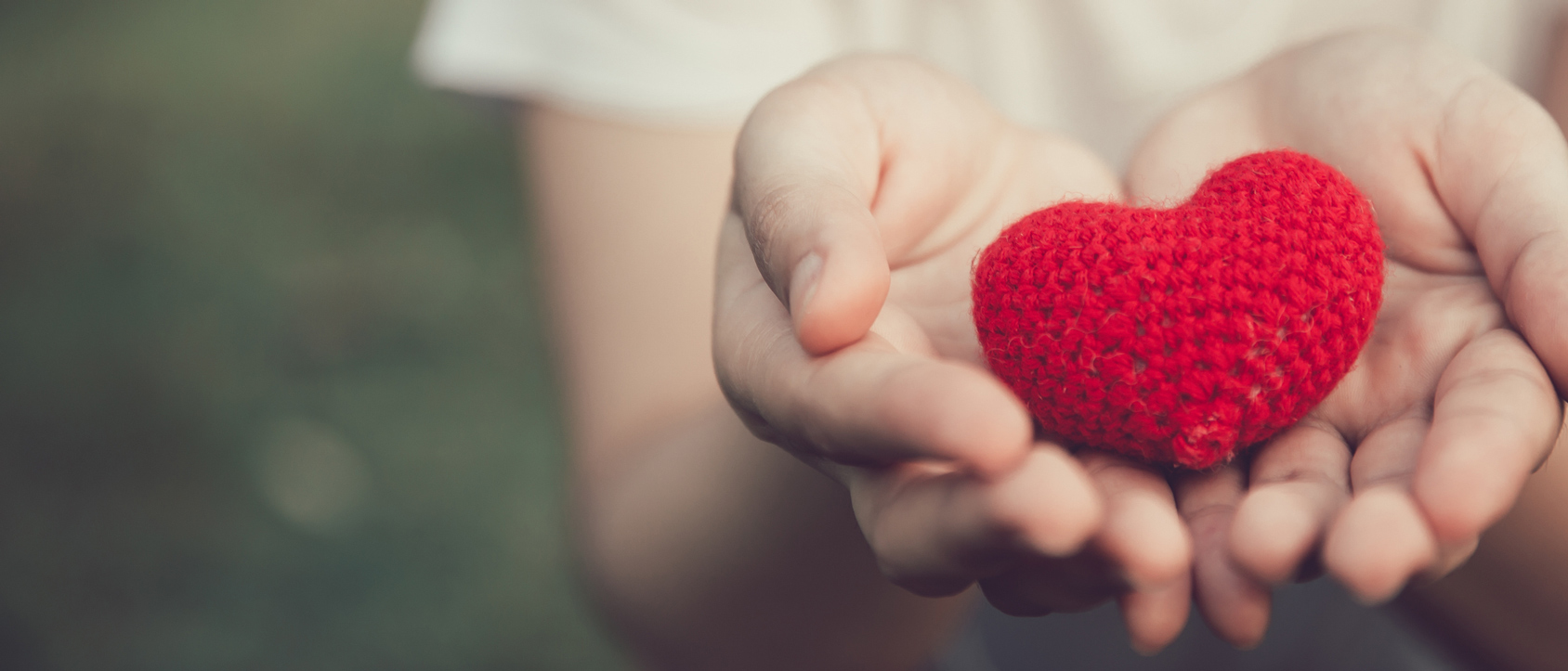 A crocheted heart being held out in cupped hands.