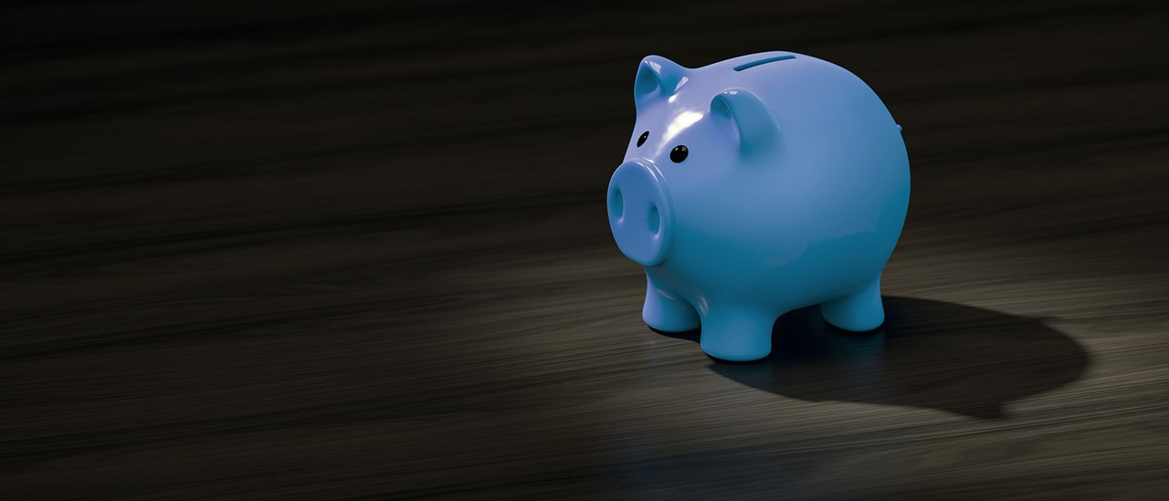 A blue piggy bank money box sitting on a desk.