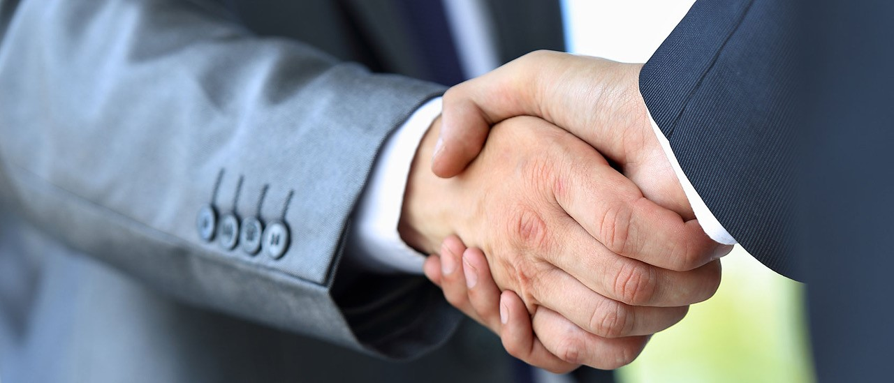 Two males in business suits shaking hands.